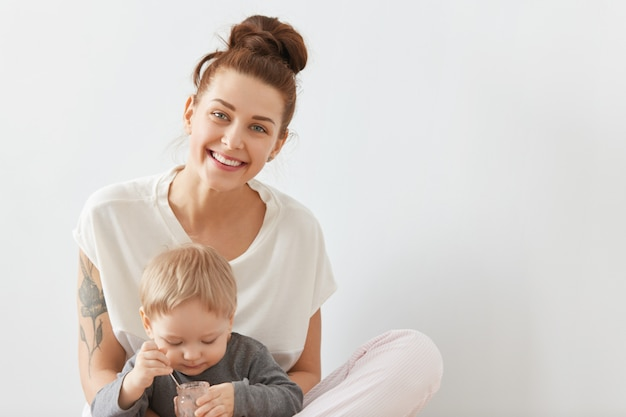 Mãe sorridente, preocupada com seu filho de três anos na parede branca. linda criança loira de camisa cinza comendo nutrição infantil de lata de vidro com colher pequena.