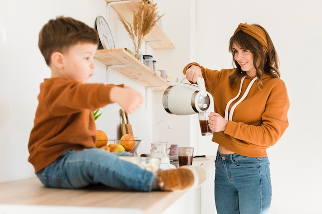 Mãe sorridente, preparando café