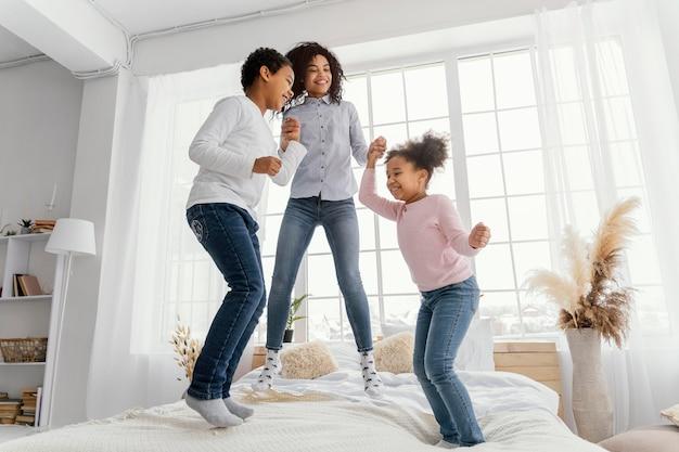 Mãe sorridente pulando na cama em casa com os filhos