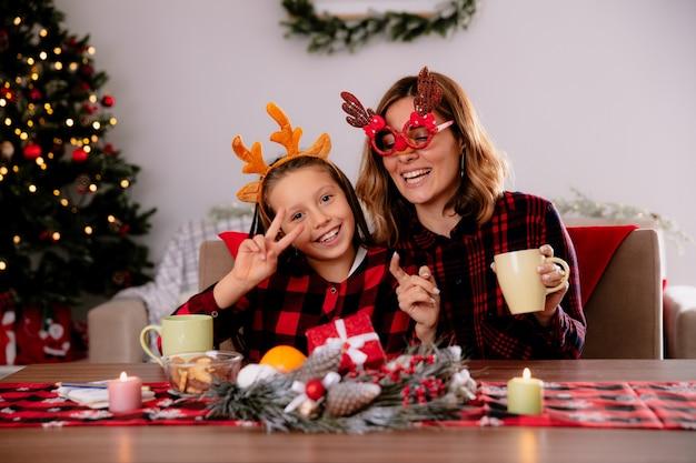 Mãe sorridente segurando copo e filha gesticulando o sinal da vitória, sentada à mesa, aproveitando o natal em casa