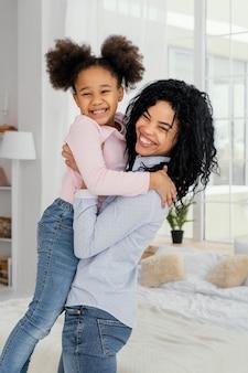 Mãe sorridente segurando sua filhinha