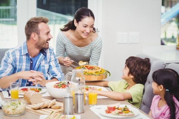 Mãe sorridente, servindo comida para crianças