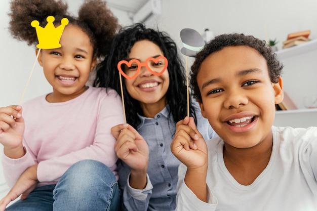 Mãe sorridente tirando selfie com os filhos em casa