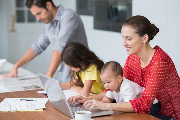 Mãe sorridente, trabalhando no laptop com bebê enquanto filha estudando