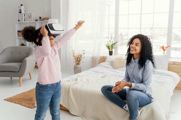 Mãe sorridente vendo a filha brincar com um fone de ouvido de realidade virtual