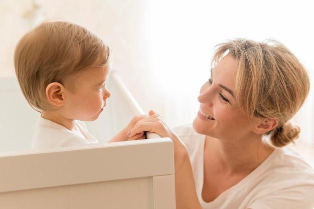 Mãe sorrindo para bebê no berço