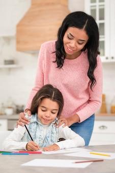 Mãe, supervisionando a filha enquanto colorir