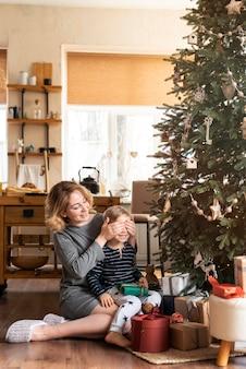 Mãe surpreendente menino com presente ao lado da árvore de natal