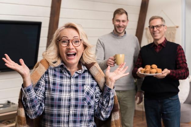 Mãe surpresa com filho e pai segurando bolos