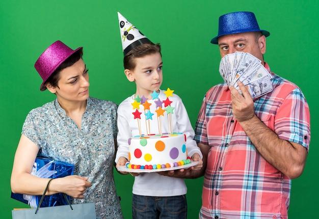 Mãe surpresa usando chapéu de festa roxo segurando uma caixa de presente e o filho usando boné de festa segurando bolo de aniversário olhando para o pai usando chapéu de festa azul e segurando dinheiro na parede verde