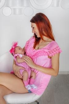Mãe tem bebê em seus braços.