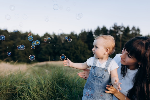 Mãe tem filhinha nos braços enquanto balões de sabão voam em volta deles