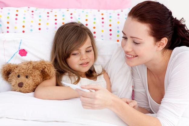Mãe tendo a temperatura da filha