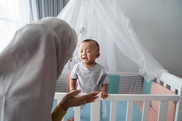 Mãe tenta consolar seu filho chorando no berço