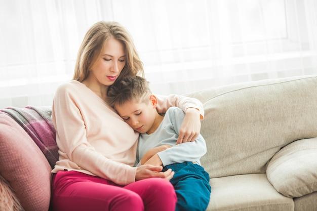 Mãe tentando acalmar o filho pequeno. mãe abraçando seu filho em casa