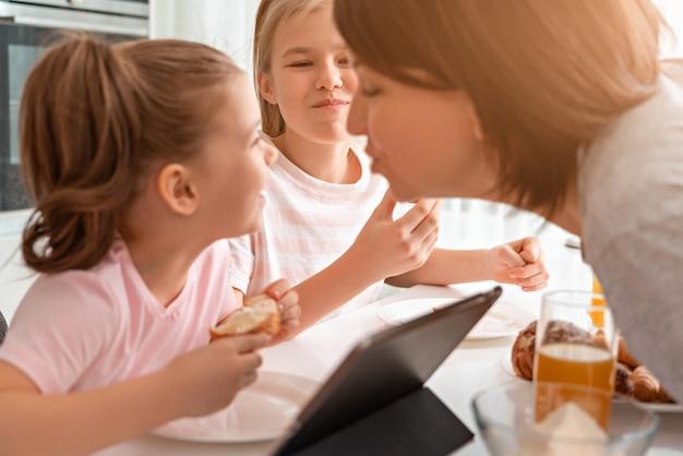Mãe tentando beijar a filha enquanto tomando café da manhã, juntamente com dois filhos