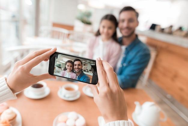 Mãe tira fotos de sua família no smartphone.