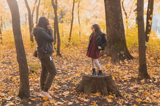 Mãe tirando fotos de sua filha carismática na câmera retro no outono park. hobbies e conceito de lazer.
