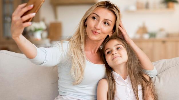 Mãe tirando selfie com a filha em casa