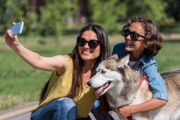 Mãe tirando selfie do filho e do cachorro no parque