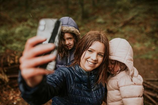 Mãe tirando selfies com as filhas nas férias em família na floresta