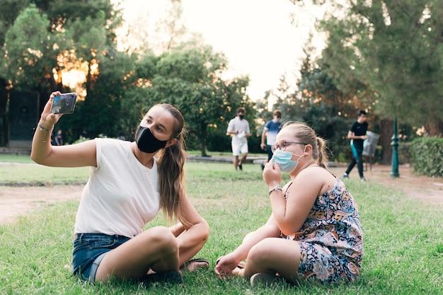Mãe tirando uma foto com a filha em um parque.