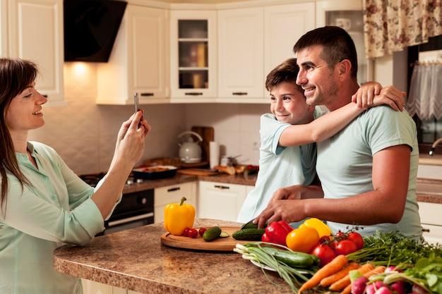 Mãe tirando uma foto de pai e filho na cozinha