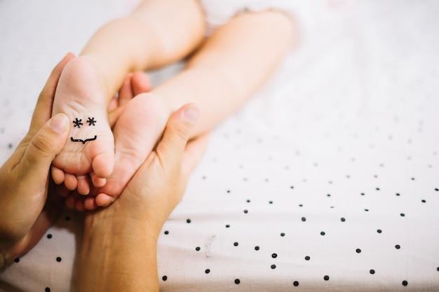 Mãe tocando os pés do bebê com o smiley