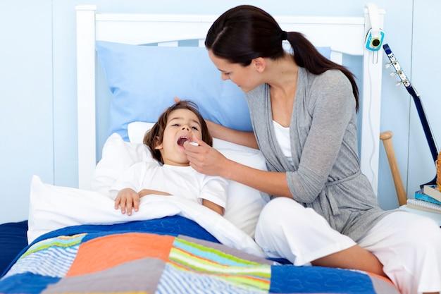Mãe tomando a temperatura do filho com um termômetro