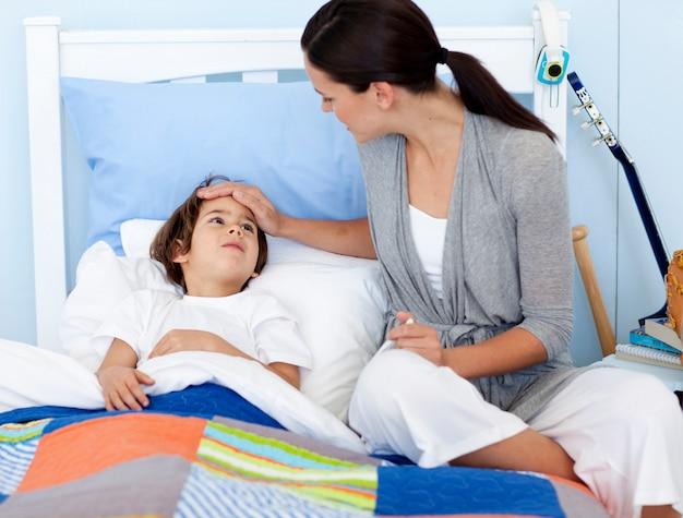 Mãe tomando a temperatura do filho