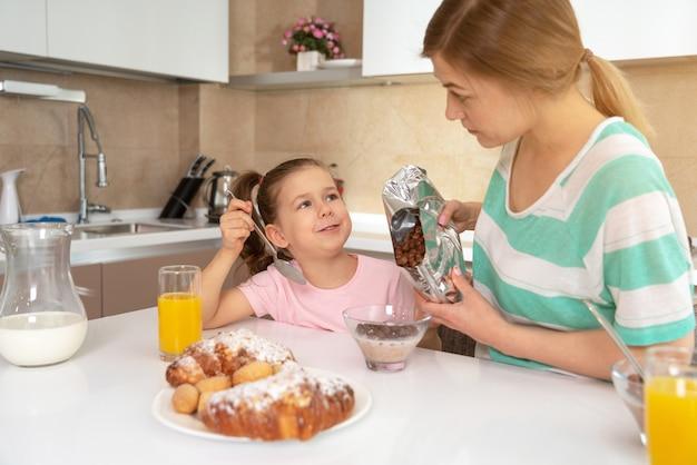 Mãe tomando café da manhã com a filha em uma mesa na cozinha, o conceito de mãe solteira feliz