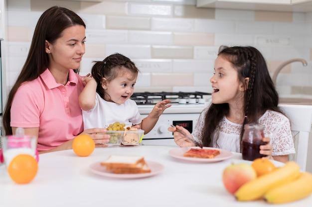 Mãe tomando café da manhã com filhas