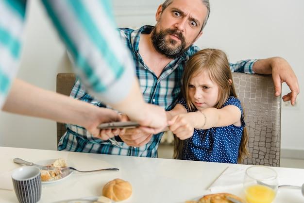 Mãe tomando tablet digital longe da filha e pai