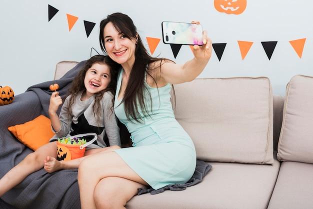 Mãe tomando uma selfie com a filha no dia das bruxas