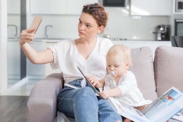 Mãe tomando uma selfie com bebê fofo