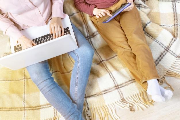 Mãe trabalha em um laptop e seu filho joga em um tablet, trabalho remoto em casa, freelance.