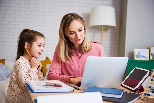 Mãe trabalhando com filha pequena no interior de casa
