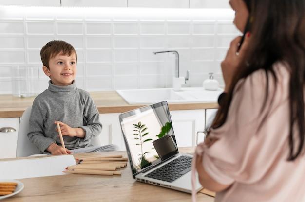 Mãe trabalhando com laptop de perto