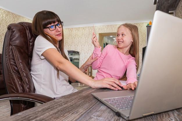 Mãe trabalhando em casa com crianças. quarentena e escola fechada durante surto de coronavírus. as crianças fazem barulho e incomodam a mulher no trabalho. ensino doméstico e trabalho freelance. menina brincando. trabalho distante