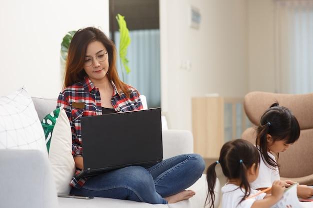 Mãe trabalhando em casa com crianças. quarentena e escola fechada durante surto de coronavírus. as crianças fazem barulho e incomodam a mulher no trabalho. ensino doméstico e trabalho freelance.