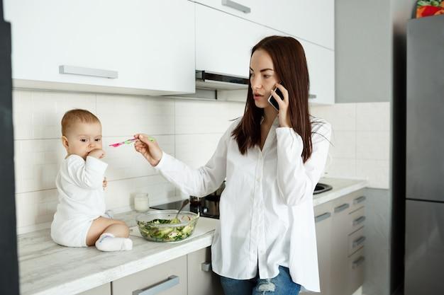 Mãe trabalhando em casa, falando ao telefone e alimentando um lindo bebê