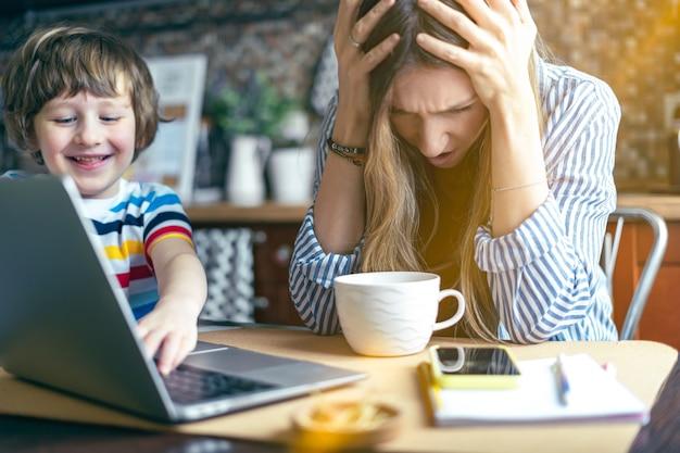 Mãe trabalhando em casa online com a criança. estressado com laptop