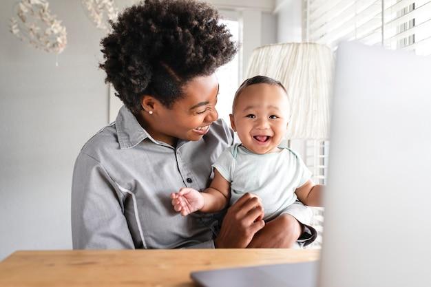 Mãe trabalhando em casa remotamente com filho