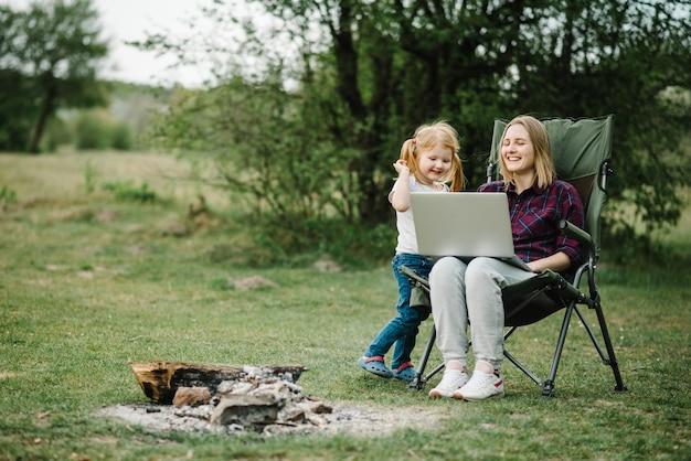 Mãe trabalhando na internet com criança ao ar livre