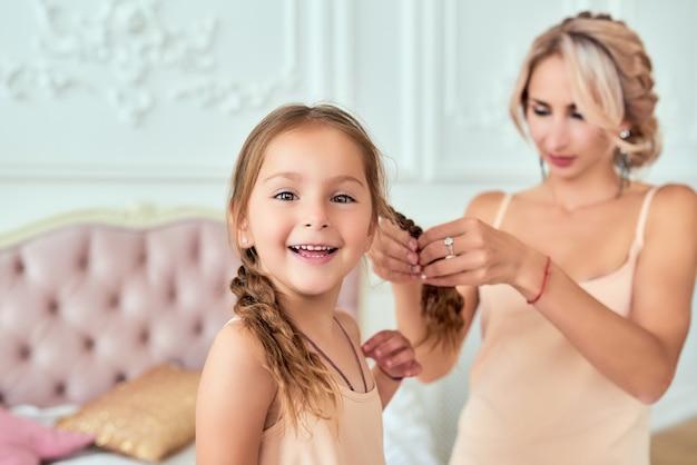 Mãe tranças tranças para fofa filha sorridente