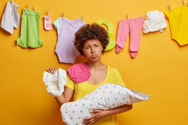 Mãe triste e chateada troca a fralda, cansada de amamentar o bebê, segura o recém-nascido enrolado em um cobertor, quer tirar uma soneca após uma noite sem dormir, tem expressão de fadiga, posa dentro de casa. conceito de maternidade e cansaço