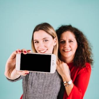 Mãe turva e filha posando para selfie