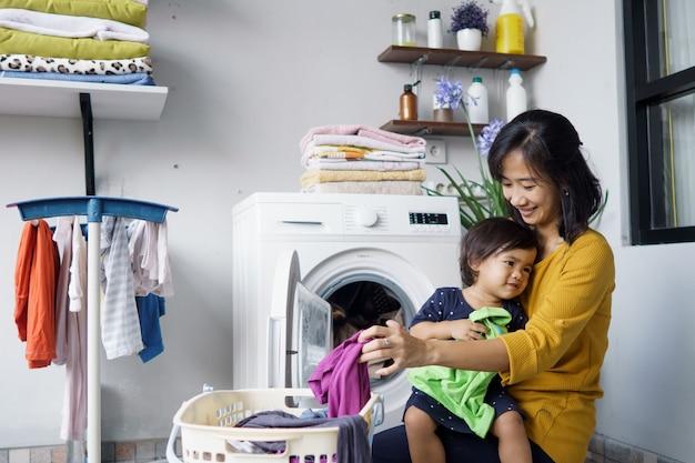 Mãe, uma dona de casa com um bebê trabalhando na lavanderia com máquina de lavar