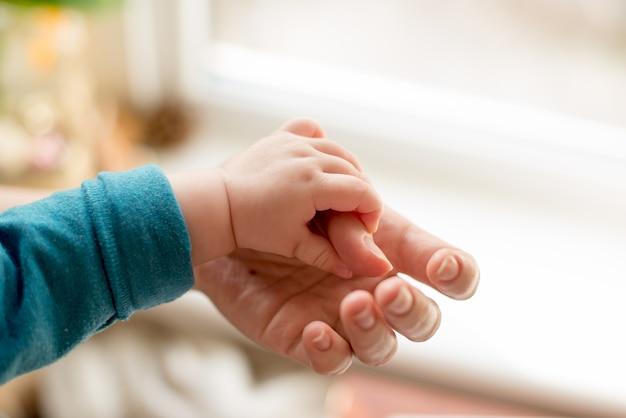 Mãe usa a mão para segurar a pequena mão do bebê para fazê-lo sentir seu amor, quente e seguro.