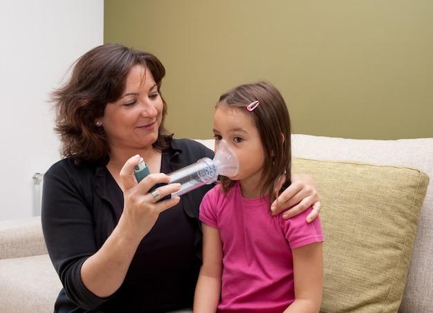 Mãe usando o inalador com a filha asmática